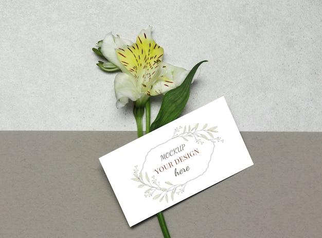 Cartão de negócios de maquete com flor em fundo bege cinza Psd Premium