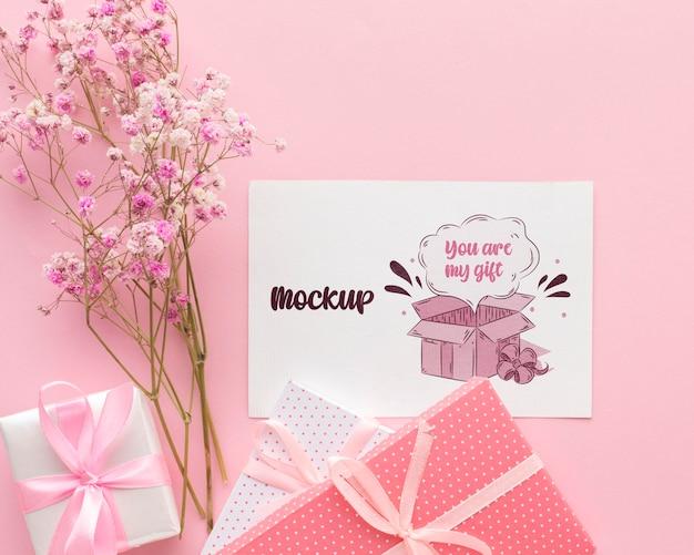 Cartão fofo de mock-up com presente embrulhado e flores Psd grátis