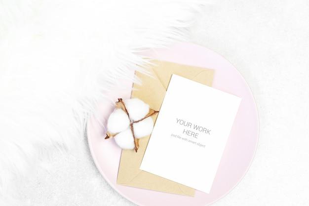 Cartão postal de maquete com envelope e algodão no prato rosa Psd Premium