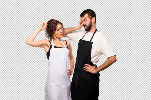 Casal de cozinheiros tendo dúvidas e com confundir o rosto enquanto coçando a cabeça Psd Premium