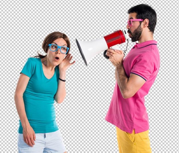 Casal em roupas coloridas, gritando pelo megafone Psd Premium