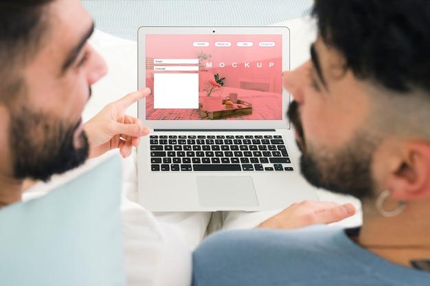 Casal gay e laptop maquete Psd grátis