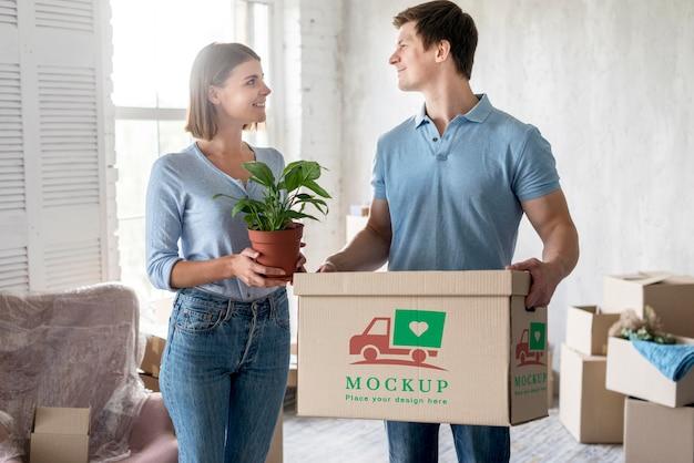 Casal segurando plantas e uma caixa com objetos para seu novo lar Psd grátis