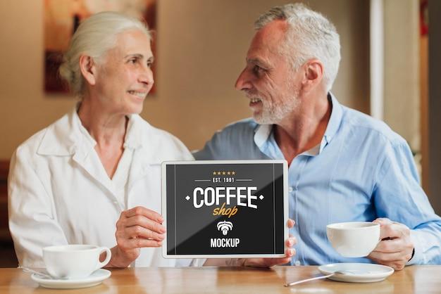 Casal segurando uma maquete de celular no café Psd Premium