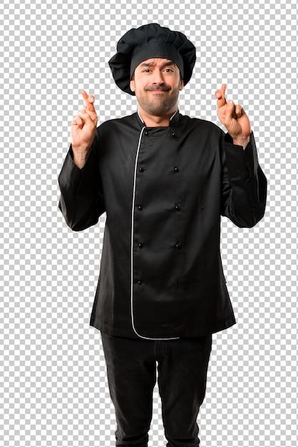 Chef man em uniforme preto com os dedos cruzando e desejando o melhor. fazendo um desejo. Psd Premium