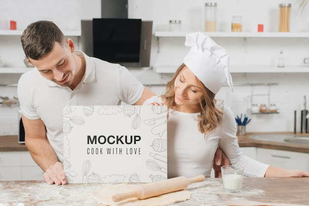 Chefs masculinos e femininos segurando um cartaz em branco na cozinha Psd grátis