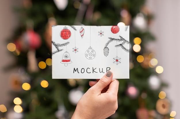 Close-up de mão segurando um cartão de natal Psd Premium
