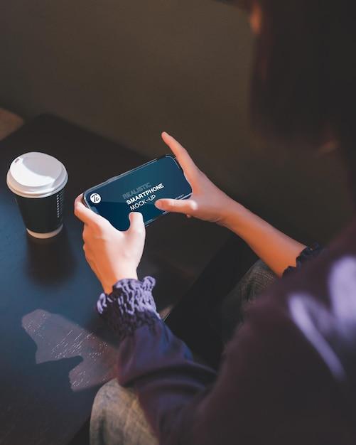 Close-up de uma mulher usando smartphone em um café Psd Premium
