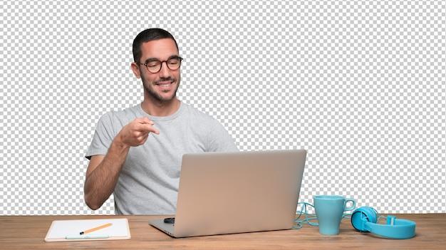 Confiante jovem sentado em sua mesa e apontando com a mão Psd Premium