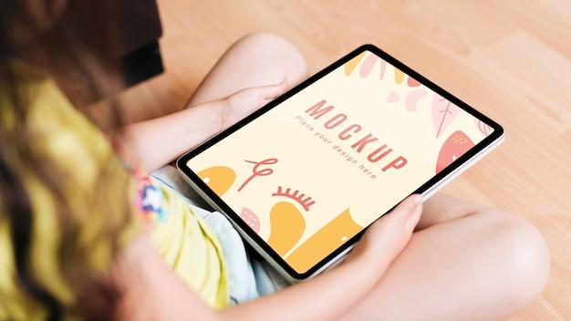 Criança segurando uma maquete digital de tablet Psd Premium