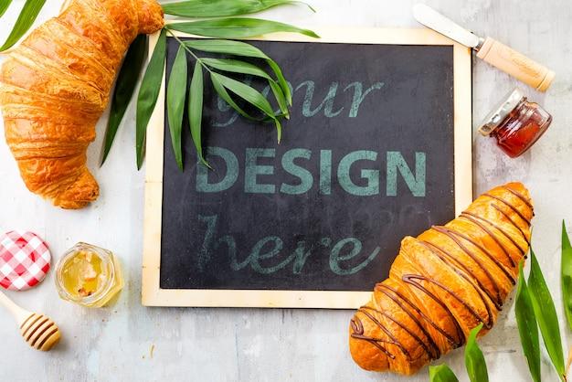 Croissant e geléia com folhas de palmeira, placa de giz plana colocar maquete Psd Premium