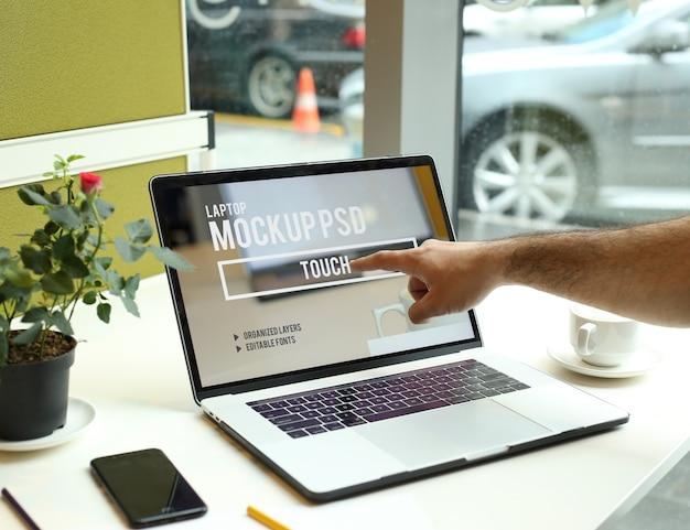 Dedo, tocando no laptop no espaço de trabalho na maquete do escritório psd Psd Premium