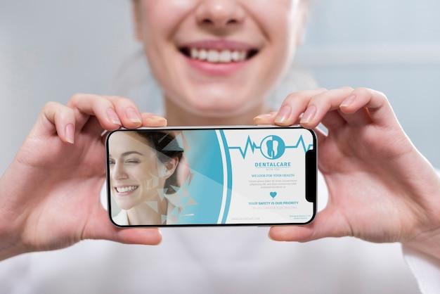 Dentista de close-up, segurando um modelo de smartphone Psd grátis