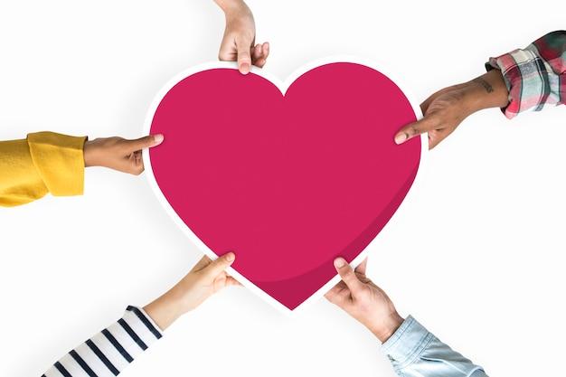 Diversas mãos segurando um coração vermelho Psd Premium