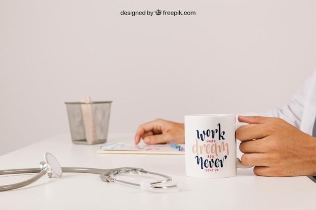 Doutor em sua mesa com caneca de café e prancheta Psd grátis