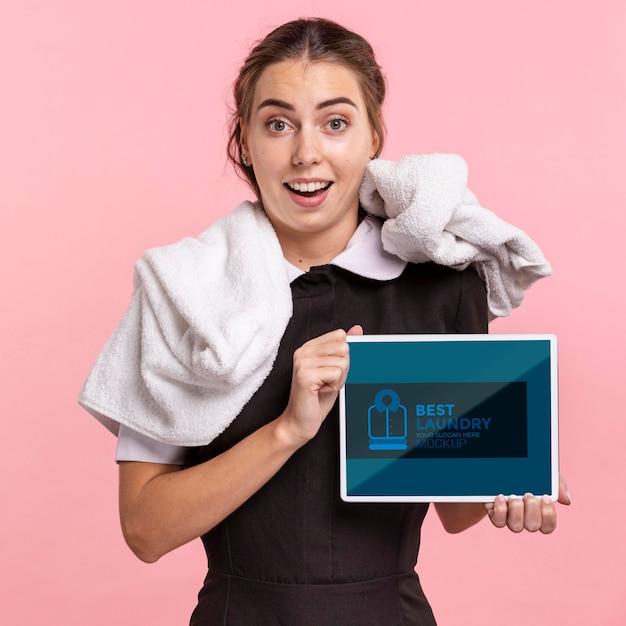 Empregada de frente com toalha segurando a maquete do tablet Psd grátis