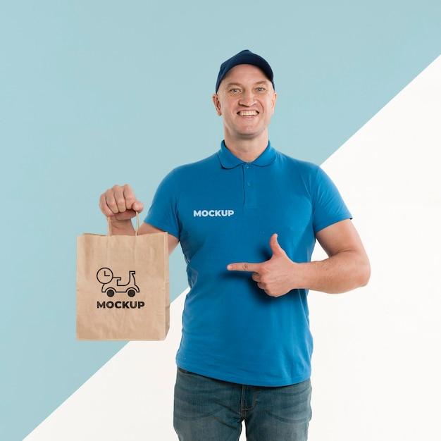 Entregador apontando para uma sacola de compras Psd Premium