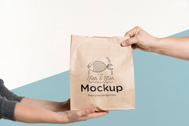 Entregador entregando uma sacola de comida para um cliente Psd grátis