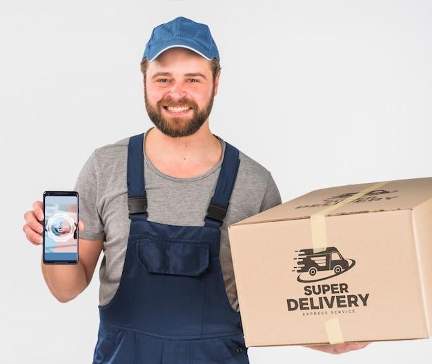 Entregador segurando maquete de smartphone para o dia do trabalho Psd grátis