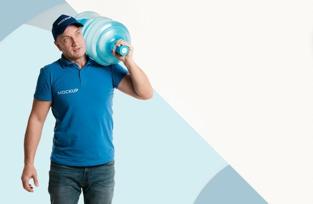 Entregador segurando uma garrafa de água Psd grátis