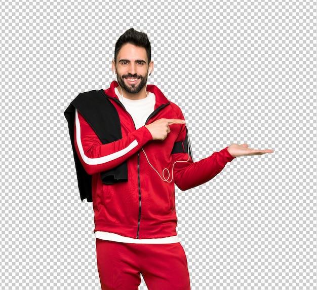 Esportista bonita segurando copyspace imaginário na palma da mão para inserir um anúncio Psd Premium