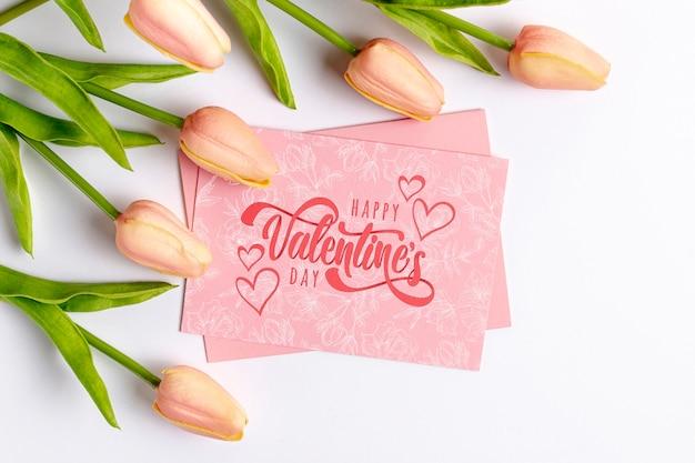Feliz dia dos namorados letras no cartão rosa ao lado de tulipas Psd grátis
