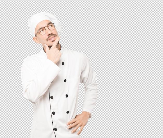 Feliz jovem chef fazendo um gesto de dúvida Psd Premium