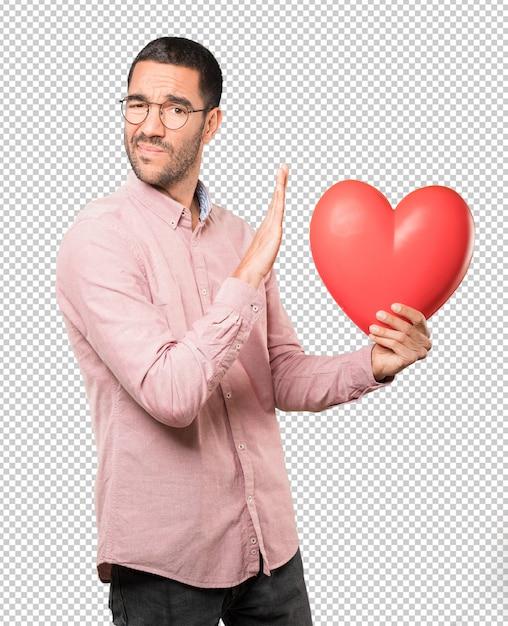 Feliz jovem segurando um coração grande brinquedo e fazendo gestos sobre o dia dos namorados Psd Premium