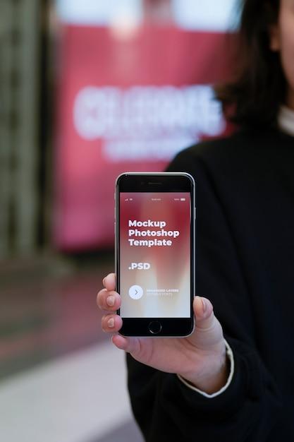 Fêmea leva smartphone moderno na mão direita Psd Premium