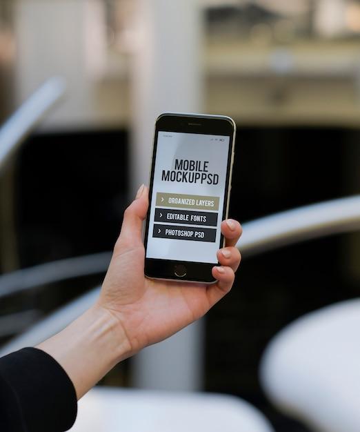 Feminino mão segurando o telefone móvel Psd Premium