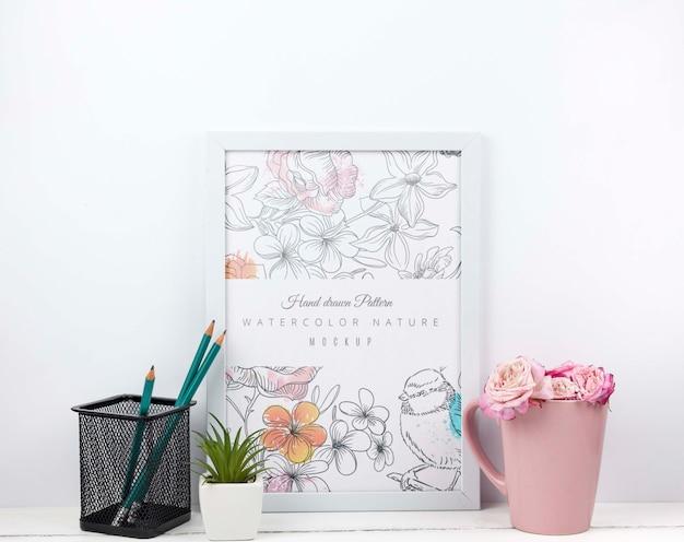 Flores em um copo ao lado da maquete do quadro Psd grátis