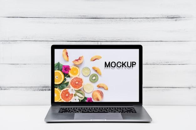 Frente vista mock-up laptop com fundo de madeira Psd grátis
