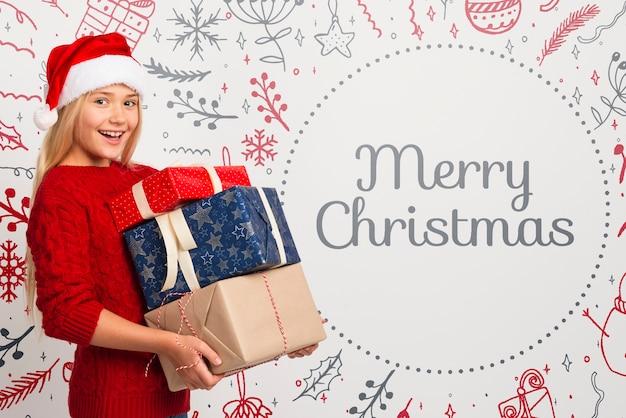 Garota feliz, segurando a pilha de presentes para o natal Psd grátis