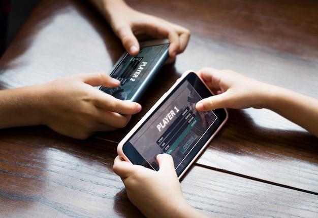 Garoto jogando um jogo para celular contra sua irmã Psd grátis