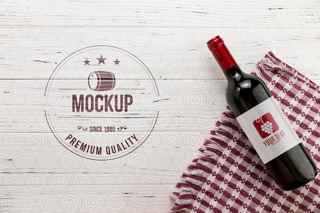 Garrafa de vinho tinto de vista frontal e toalha de cozinha Psd Premium