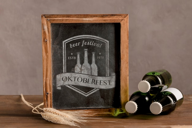 Garrafas de cerveja ao lado do quadro de oktoberfest Psd grátis