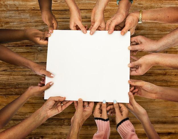 Grupo de diversidade mãos segurando papel vazio Psd grátis