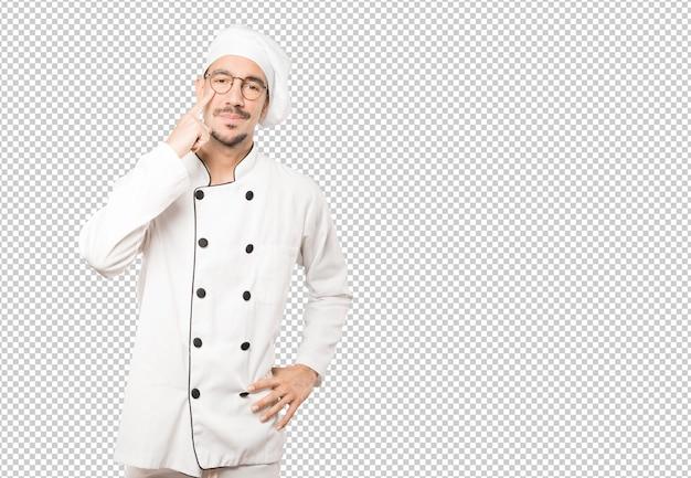 Hesitante jovem chef fazendo um gesto de cuidado com a mão apontando para o olho Psd Premium