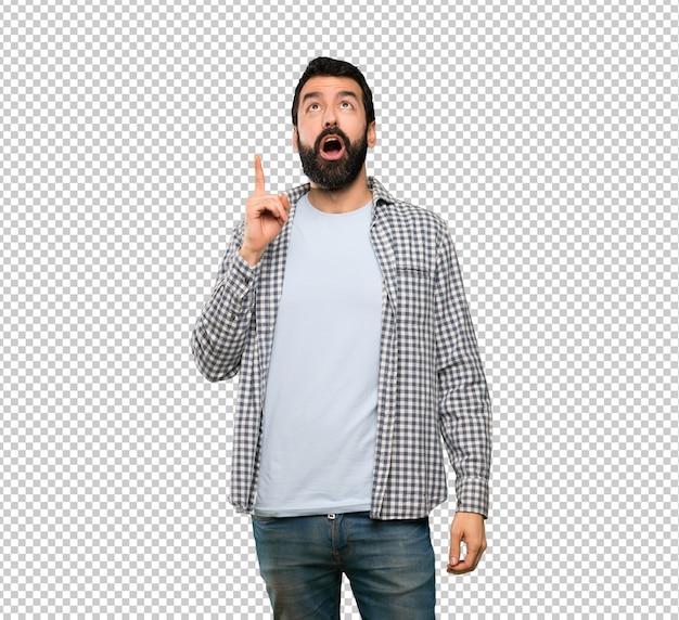 Homem bonito com barba apontando para cima e surpreso Psd Premium