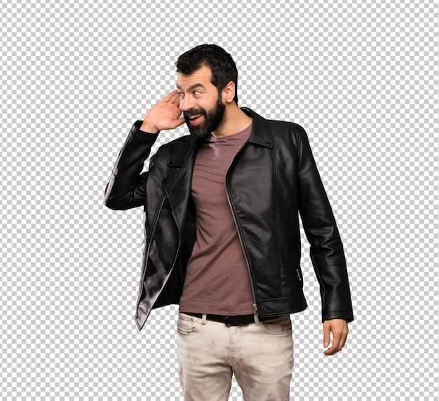 Homem bonito com barba ouvindo algo, colocando a mão na orelha Psd Premium