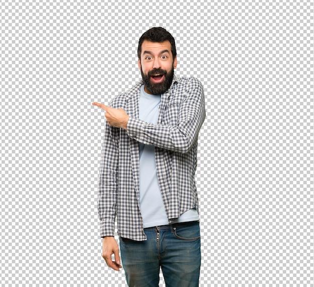 Homem bonito com barba surpresa e apontando o lado Psd Premium