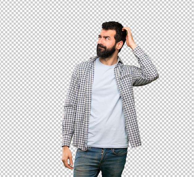 Homem bonito com barba tendo dúvidas enquanto coçando a cabeça Psd Premium