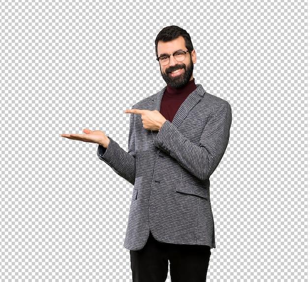Homem bonito com óculos segurando copyspace imaginário na palma da mão para inserir um anúncio Psd Premium