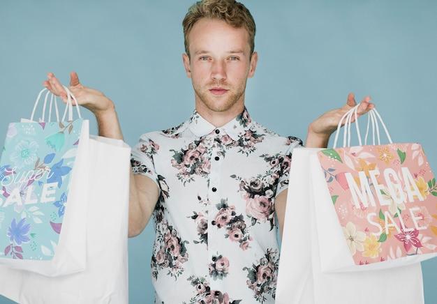 Homem bonito, segurando várias sacolas de compras Psd grátis