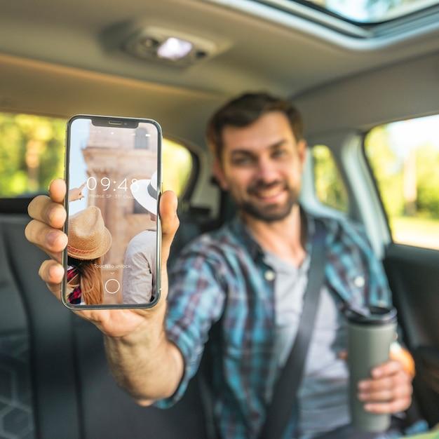 Homem, carro, mostrando, smartphone, mockup Psd grátis