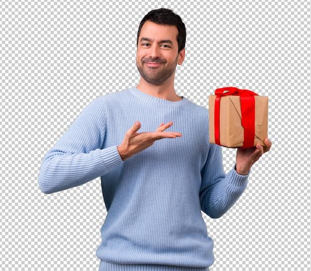 Homem com camisola azul segurando caixas de presente nas mãos Psd Premium