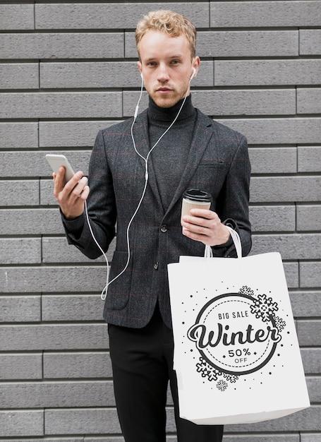 Homem com sacolas de compras e segurando móvel Psd grátis