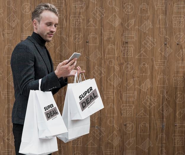 Homem com sacolas de compras, verificação de telefone Psd grátis