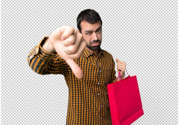 Homem com sacos de compras, mostrando o polegar baixo sinal com expressão negativa Psd Premium