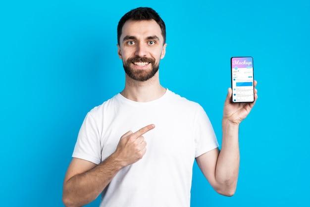 Homem de camisa branca mostrando a vista frontal do celular Psd grátis